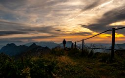 guy silhouette watching at panorama view from a the top of mountain to lake during sunset, brienzer rothorn switzerland stock photo
