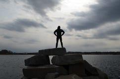 Guy Silhouetted em uma pose do super-herói em um molhe da rocha imagem de stock