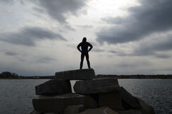 Guy Silhouetted in a Super Hero Pose on a Rock Jetty. Guy silhouetted againsta  stormy sky in a super hero pose on a rock jetty Stock Image