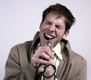 Guy singing. A young guy singing into a microphone stock image