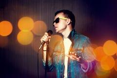 Guy Singing met Microfoon De achtergrond van Bokeh Stock Fotografie