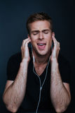 Guy is singing to his favourite song listening to it on earphone. S with black v-neck shirt on dark background Royalty Free Stock Photo