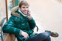 Guy sit bench interact smartphone. Communication concept. Hipster use smartphone on winter day. Man handsome hold. Smartphone. Man unshaven wear warm jacket and stock photo