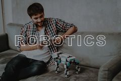 Guy. Sit. Couch. Tablet. Robot. Robots. Play. royalty free stock images