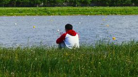 A man sits and uses a smartphone outdoors in the park stock video footage