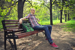 Guy sits on a bench in park Stock Photo