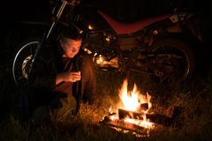 The guy sits with cup of tea by the fire and motorcycle at night Royalty Free Stock Images