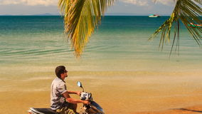 Guy Sits on Motorbike Smiles Touches Palm Branch under Palm. Closeup guy sits on motorbike under palm touches branch against boat on skyline in azure sea stock video