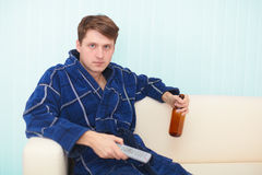 Guy sits on sofa and drinks beer looking TV Royalty Free Stock Photo