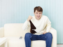 Guy sits on sofa and watches football on TV Stock Photography