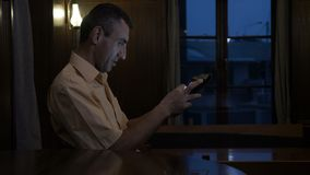 Guy sitting alone at a table in a pub and watching a tablet pc -. Guy sitting alone at a table in a pub and watching a tablet pc stock footage