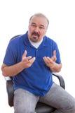 Guy Sitting barbudo en silla que explica algo Foto de archivo