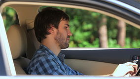 Guy sitting in the car running on the tablet stock footage