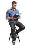 Guy sitting on a chair and reading a book Stock Photos