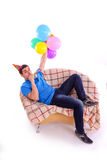 Guy sitting on the couch with a hat and balloons a Royalty Free Stock Photography