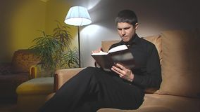 The guy sitting on the couch and looking for something in the book. stock video