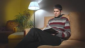 The guy sitting on the couch and reading a book. stock video