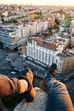 The guy is sitting on the edge of a tall building. He hung his legs with beautiful black sneakers over the city. High altitude and danger Stock Images