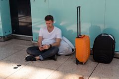 The guy is sitting on the floor at the airport. Brunette in a white T-shirt royalty free stock photography