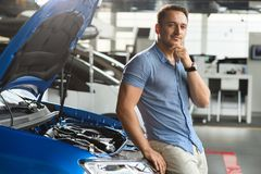 Guy is sitting on the front of the brandnew car. royalty free stock photography