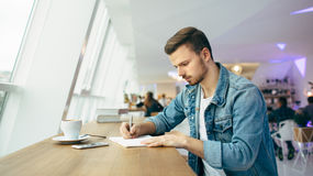 Guy is sitting in front of the table near window Royalty Free Stock Images