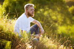 Guy sitting on the grass Royalty Free Stock Photos