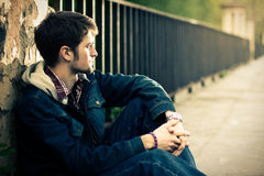 Guy sitting near the fence. Young man sitting near the fence in sunlight Stock Image
