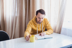 Guy sitting near the window at table and reads Stock Photos