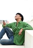 Guy sitting outdoors listening to music Royalty Free Stock Photos