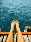 Man legs pier. Guy is sitting on the pier. Blue ocean stock photos