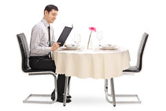 Guy sitting at a restaurant table. Young guy sitting at a restaurant table and reading the menu isolated on white background Stock Images