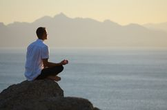 Guy sitting on a rock in the lotus position Royalty Free Stock Photos