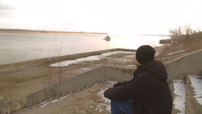 The guy sitting on the shore, the boat floats, the boy at the river, alone stock footage