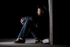 Guy sitting on skateboard Royalty Free Stock Photo