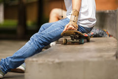 Guy sitting on skateboard outdors and wearing hands sports protection. Outdors image of guy sitting on skateboard wearing sports protection on hand Royalty Free Stock Image