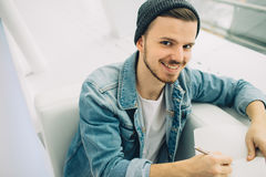 Guy is sitting on sofa and writing notes. Smiling man is sitting close up on sofa and looking at camera writing down some notes. He is happy young student Stock Photography