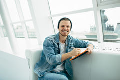 Guy is sitting on sofa and writing notes. Smiling man is sitting on sofa and writing down some notes. He is happy young student Stock Photography