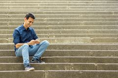 Guy sitting on stairs with smartphone stock image