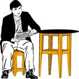 a guy sitting on a stool at the table Royalty Free Stock Photo