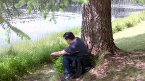 Guy sitting under tree near a lake stock footage