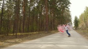 Guy skate on logboard in a forest with a color smoke grenade , slow motion stock footage