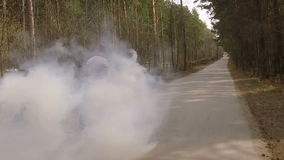 Guy skate on logboard in a forest with a color smoke grenade , slow motion. Man skate on logboard on the road with a color smoke grenade , slow motion stock footage