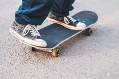 Guy on a skateboard. Teenager doing exercises on a skateboard on the road Stock Photo