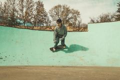 Guy practicing skateboarding and doing tricks in a skatepark royalty free stock photo