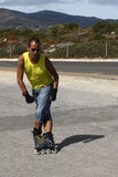 Guy skating in-line breaking. Backwards Royalty Free Stock Image