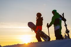 The guy skier and girl snowboarder on the background of the sunset sky. Sheregesh Russia royalty free stock images