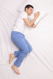 Guy sleeping on a comfortable bed. Vertical shot of a calm young guy sleeping on a comfortable bed Royalty Free Stock Image