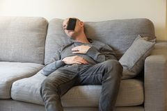 A guy is sleeping on a couch with a smartphone on his face royalty free stock photos