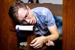 Guy Sleeping no banco de igreja quando na igreja fotografia de stock