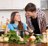 Guy and smile girl cooking Royalty Free Stock Photos